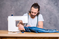 Young tailor with sewing machine Stock Photos