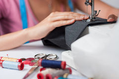 Young tailor sews a pair of trousers, horizontal royalty free stock images