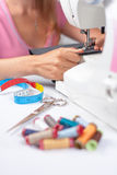 Young tailor sews a pair of trousers, vertical Royalty Free Stock Photos