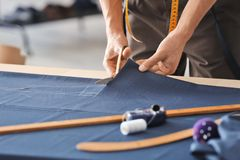 Young tailor working with textile. In atelier Stock Photos
