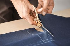 Young tailor working with textile. Closeup Stock Image