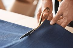 Young tailor working with textile. Closeup Stock Photo