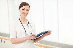 Young and talented doctor. Beautiful young female doctor holding Royalty Free Stock Images