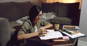 Young talented female artist drawing pencil sketches sitting on the floor in the evening at home. Designer or Illustrator working