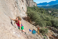 Young talented Female Rock Climber ascending rocky Wall Royalty Free Stock Photos
