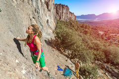Young talented Female Rock Climber ascending rocky Wall Royalty Free Stock Images