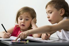 Young talents. Careful brother shows to his smaller sister the color of felt-tip pen which is better for her drawing Royalty Free Stock Image