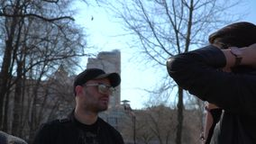 Young talks on phone standing near friends. Handsome guy in cap and sunglasses looks on the girl and waits when she finish her conversation. People are stock video footage
