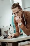 Young tall dressmaker in eyeglasses thinking about fabric for a new dress. Right choice. Young tall dressmaker in eyeglasses looking involved while thinking stock image