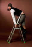 Young tall girl in cap climbing on high ladder Stock Image