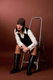 Young tall girl in cap sitting on ladder with head Royalty Free Stock Images