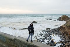 The guy is walking along the pier in virtual reality glasses. A young tall guy goes alone on a pier by the sea in virtual reality glasses Stock Images
