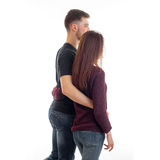 Young tall guy keeps waist girl with long hair and they are turning back forward. Isolated on white background Royalty Free Stock Photo