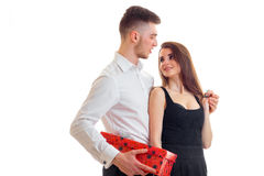 Young tall guy in a white shirt brought girl red gift box. Isolated on white background Royalty Free Stock Photography
