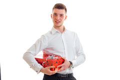 Young tall guy in a white shirt holding a red gift box. On white background Royalty Free Stock Image