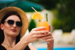 Young tan model in stylish summer outfit enjoying pool party , holding tasty alcohol cocktail . stock image