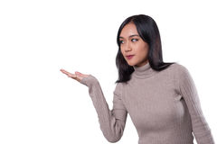 Young tan skin Asian woman with casual cloths. Young attractive tan skin Asian woman with casual cloths is showing a gesture to present something. Person gesture Stock Photo