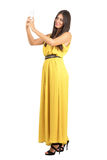 Young tanned beauty in yellow dress taking photo with mobile phone Royalty Free Stock Images