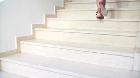 Young tanned female feet in sandals go up the stairs stock footage