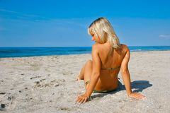 Young tanned girl. On sandy beach Stock Image