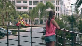 Young tanned lady with long hair leans on balcony fence stock video