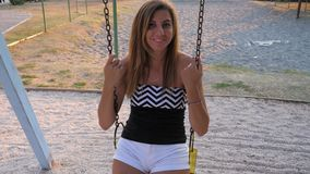 Young Tanned Smiling Woman Swinging On A Swing. A young tanned smiling woman brunette swings on a swing. Slow motion, 4K, 3840x2160 stock footage