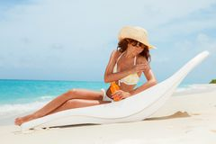 Young tanned woman in bikini sit at chaise-longue. And apply sun-protection cream to her skin on the beach. Happy woman vacation at Paradise. Relax on the beach stock photos