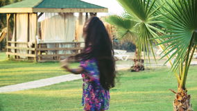 Young tanned woman with long hair dancing between tropical palm trees in summer stock video footage