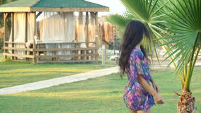 Young tanned woman with long hair dancing between tropical palm trees in summer. Young tanned woman with long hair dancing between tropical palm trees in the stock video footage