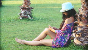 Young tanned woman with long hair sitting under tropical palm trees in summer. she uses smartphone stock video