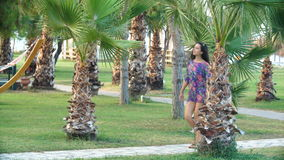Young tanned woman with long hair walks along path between tropical palm trees stock video