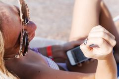 A young tanned woman looks at her nail-manicure and laughs at th royalty free stock photography