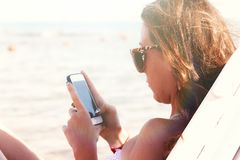 A young tanned woman looks into a smartphone through sunglasses stock photos