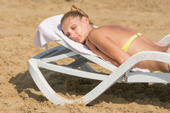 Young tanned woman lying on deck chair with his eyes closed on the beach Royalty Free Stock Photography
