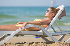 Young tanned woman lying relaxed on sun lounger on the beach Stock Photo