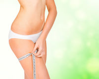 Young tanned woman measuring her body Royalty Free Stock Images