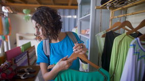 Young tanned woman with short black hair, who dressed blue dress and a schoolbag behind thoughtfully chooses clothes in. A small Asian shop stock footage