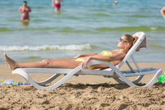 Young tanned woman sunbathing on sun lounger on the beach against the backdrop of people bathing Royalty Free Stock Image