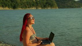Young tanned woman at sunset working remotely on the lake