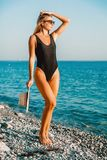 Young tanned woman in swimsuit on tropical beach, resort fashion style. Beautiful girl. Young tanned woman in swimsuit on tropical beach, resort fashion style Stock Photography
