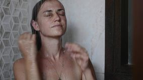 Young tanned woman is taking a shower with close eyes. stock video