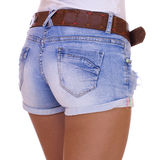 Young tanned woman wearing blue short jean on white background Stock Photo