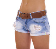 Young tanned woman wearing blue short jean on white background Stock Photos