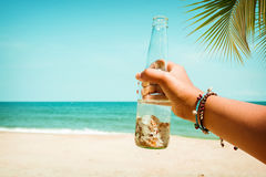Young tanned women hand holding bottle with seashell at tropical beach in summer. Stock Images