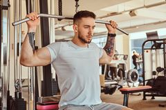 Young tattoed man is doing exercise for back on training apparatus in gym.  royalty free stock photo