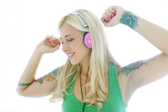 Young tattoed woman. Dancing with headphones isolated on white stock images