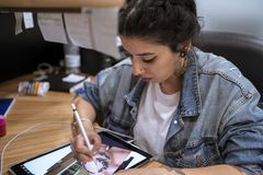 Young tattoo artist drawing her new design on the tablet. royalty free stock photo