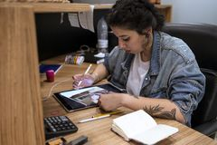 Young tattoo artist drawing her new design on the tablet. stock photos