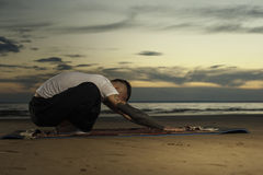 Young tattoo man practicing yoga pose on the beach Stock Images
