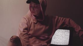 Young tattooed woman sitting near working static tv set in dark room. Young tattooed caucasian woman with glitter on face in pink hoodie and black cap sitting stock video footage